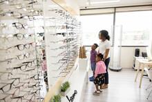 Mother And Kids Looking At Eyeglasses Display In Optometry Center