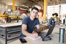 Portrait Confident Male Woodworker At Laptop In Wood Shop
