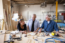 Happy Woodworkers Talking At Workbench In Workshop
