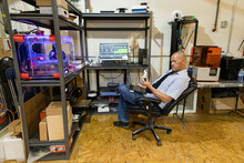 Male Maker Looking At 3D Fabrication In Workshop