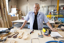 Portrait Confident Male Woodworker With Wooden Spoons In Workshop