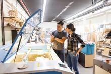 Makers Talking At 3D Printer In Workshop