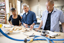 Woodworkers With Equipment At Workbench In Workshop