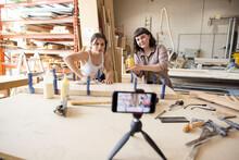 Female Woodworkers Filming Tutorial In Workshop