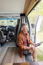 Man Sitting In Camper Van Reading Tablet