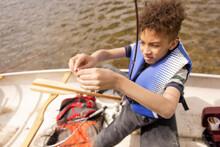 Boy Baiting Fishing Line In Canoe