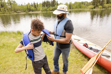 Father Fastening Sons Lifejacket Ready To Go Canoeing
