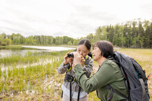 Mother And Daughter Looking At Wildlife Through Binoculars