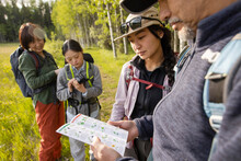 Family Looking At Guide On Country Walk