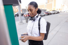Young Woman Paying For Parking On City Sidewalk