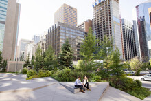 Business People In City Park Surrounded By Highrise Buildings