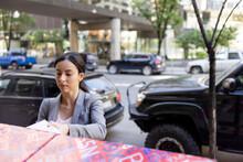 Businesswoman Placing Package In Dropbox On City Sidewalk
