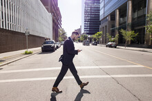 Businessman With Smart Phone Crossing Sunny City Street