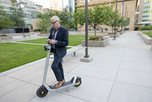 Senior Businessman With Smart Phone Renting Electric Scooter In City