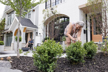 Senior Woman Trimming Bushes Outside House