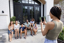Young Woman Photographing Family On Patio Steps