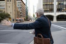 Senior Businessman Hailing Taxi On City Street Corner