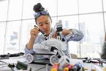 Female Engineer With Flashlight Assembling Robotics