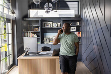 Man Talking On Smart Phone In Home Office
