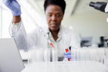 Female Scientist With Pipette Filling Test Tubes In Laboratory