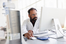 Focused Male Scientist Working At Computer In Laboratory