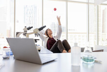 Female Scientist Tossing Stress Ball In Air In Highrise Laboratory
