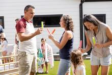 Family Enjoying Flavored Ice In Sunny Summer Backyard