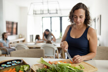 Woman Cutting Vegetables At Cutting Board In Kitchen