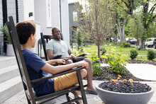 Father And Son In Rocking Chairs At Fire Pit On Patio
