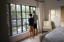 Father And Son Looking Out Bedroom Window