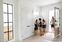 Family Returning Home At Front Door Entry