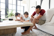 Father Watching Daughter And Son Drawing In Living Room