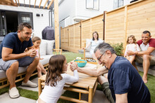 Grandfather And Granddaughter Arm Wrestling In Backyard