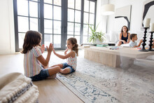 Sisters Playing Clapping Game On Living Room Floor