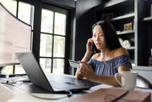 Woman With Credit Card Talking On Smart Phone At Laptop In Home Office