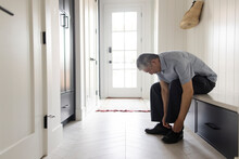 Senior Man Putting On Shoes In Mud Room