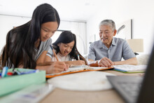 Grandfather Helping Granddaughters With Homework