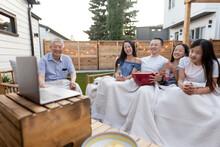 Multigenerational Family Watching Movie On Laptop In Backyard