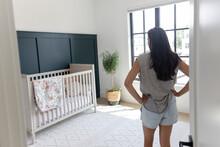 Woman Looking At Crib In Baby Nursery