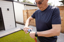 Senior Man Attaching Hose To Sprinkler In Backyard
