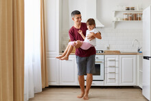 Cheerful Dad Carrying His Dark Haired Daughter, Playing With Happy Little Preschool Child Indoors Against Kitchen Set, Playful Small Kid Girl Having Fun With Smiling Father At Home.