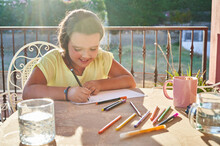 Focused Girl Drawing On Paper On Terrace In Sunlight
