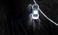 Aerial View Professional Driver Drifting Car On Wet Asphalt Road Track, Automobile And Automotive Race Car Drift On Abstract Asphalt Road Tire Skid Mark With Water Splash.