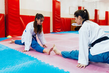 Young Women Straddle Stretch In A Dojo Wearing Taekwondo Dobok