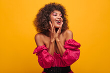 Close-up Of Amazing African Holding Her Cheeks With Two Hands Against Background Of Mustard Color. Curly-haired Brown-haired Woman With Soft Pink Make-up Is Dressed In Crimson Dress With Wide Belt.