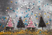 Zwei Von Vier Süßen Kuchenstücken In Der Reihe Dekoriert Als Christbäume Mit Zuckerperlen, Sternen Und Puderzucker Zur Weihnachtlichen Adventszeit