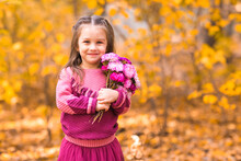 Cute Little Girl In Fall Park With Pink Flower Bouquet.