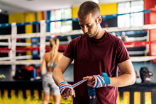 Standing Adult Man Wrapping Hands With Clored Boxing Wrap For Training In The Gym