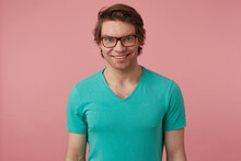 Indoor Shot Of Young Positive Male, Wears Stylish Glasses And Blue T-shirt, Looks Directly Into Camera With Broad Smile, Feels Happy. Isolated Over Pink Background