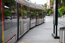 Tram Arriving At Its Station To Pick Up Passengers. Travel Concept, Public Transport, Renewable Energy And Non-polluting.